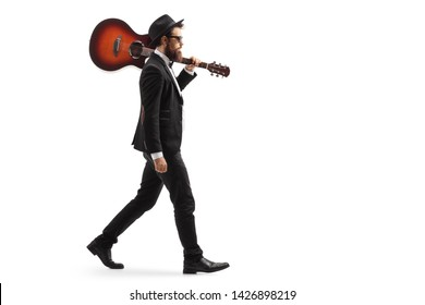 Full length profile shot of a man in a suit walking with an acoustic guitar on his shoulder isolated on white background