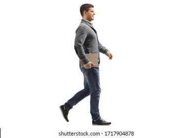 Full length profile shot of a man holding a book and walking isolated on white background