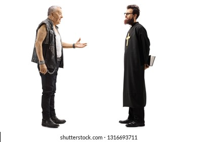 Full length profile shot of a mature male punker in a leather vest talking to a priest isolated on white background