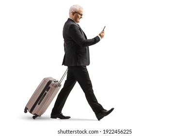 Full length profile shot of a mature businessman walking and pulling a suitcase while using a smartphone isolated on white background