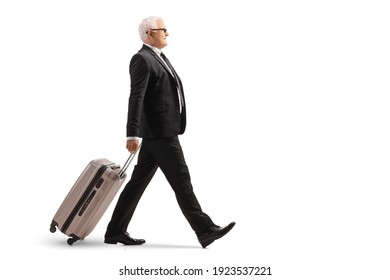 Full length profile shot of a mature businessman walking and pulling a suitcase isolated on white background