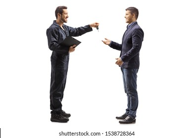 Full length profile shot of a mechanic holding a clipboard and giving keys to a male customer isolated on white background