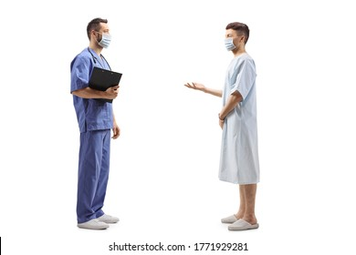 Full length profile shot of a medical worker in a blue uniform with a face mask and a patient talking isolated on white background