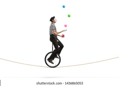 Full length profile shot of a mime riding a unicycle on a rope and juggling with balls isolated on white background - Shutterstock ID 1436865053