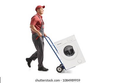Full length profile shot of a mover pushing a hand truck loaded with a washing machine isolated on white background