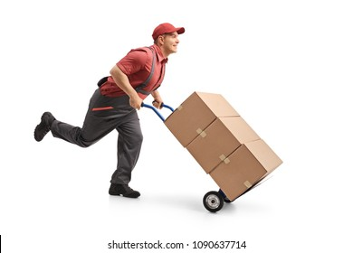 Full length profile shot of a mover running and pushing a hand truck loaded with boxes isolated on white background