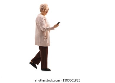 Full length profile shot of an older lady walking and using a cell phone isolated on white background