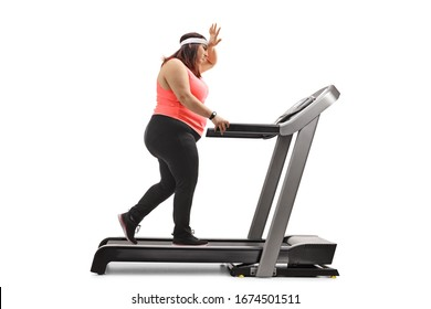 Full length profile shot of an overweight woman exercising on a treadmill and holding her forhead isolated on white background