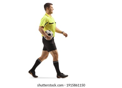 Full length profile shot of a referee holding a football and walking isolated on white background