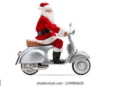 Full length profile shot of Santa Claus riding a vintage motorbike and looking at the camera isolated on white background