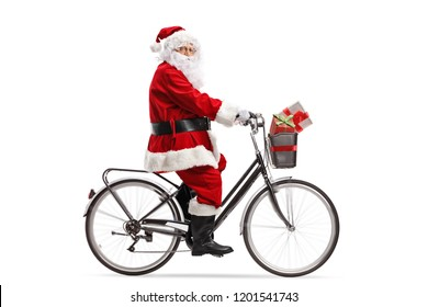 Full length profile shot of Santa Claus riding a bicycle isolated on white background