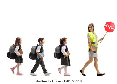 Full length profile shot of a school teacher with a safety vest and stop sign walking with schoolchildren  isolated on white background