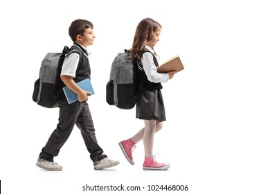 Full length profile shot a schoolboy and a schoolgirl with backpacks and books walking isolated on white background