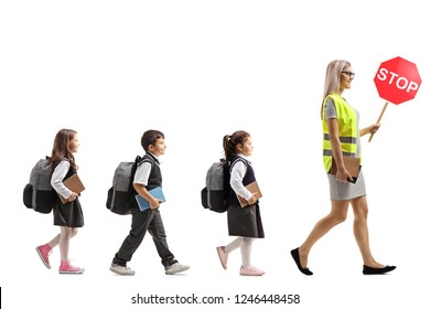 Full length profile shot of schoolchildren walking behind a female teacher with a safety vest and a stop sign isolated on white background