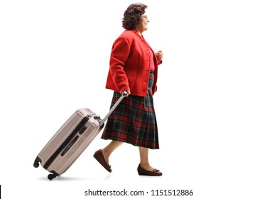 Full length profile shot of a senior lady walking and pulling a suitcase isolated on white background