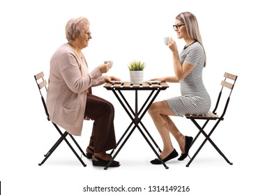 Full length profile shot of a senior woman drinking coffee with a young woman at a table isolated on white background