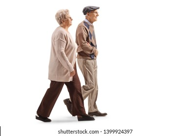 Full length profile shot of a senior husband and wife walking isolated on white background