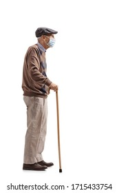 Full length profile shot of a senior man with a cane wearing a medical mask isolated on white background