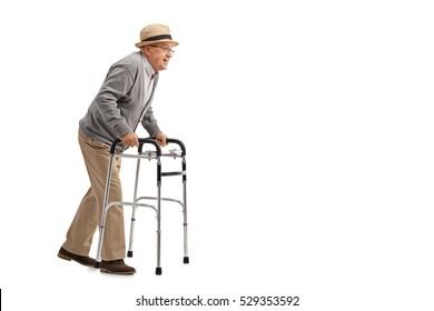 Full length profile shot of a senior walking with a walker isolated on white background