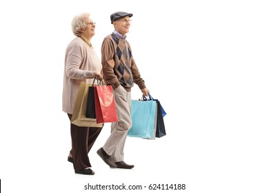 Full length profile shot of a senior couple with shopping bags walking isolated on white background