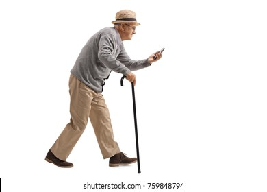 Full length profile shot of a senior with a cane walking and looking at a phone isolated on white background