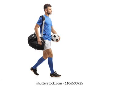 Full length profile shot of a soccer player with a bag and a football walking isolated on white background