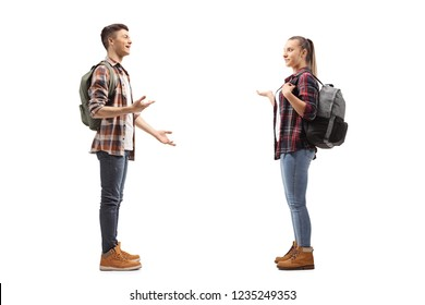 Full length profile shot of teenage students talking with each other isolated on white background