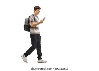 Full length profile shot of a teenage student walking and looking at a phone isolated on white background