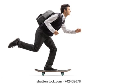 Full length profile shot of a teenage student riding a skateboard isolated on white background