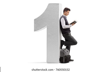 Full length profile shot of a teenage student reading a book and leaning against a cardboard number one isolated on white background