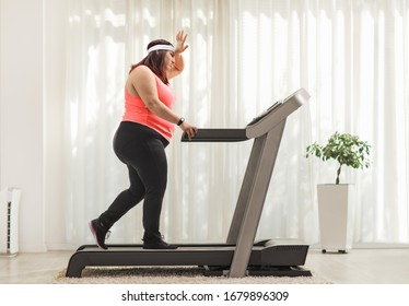 Full length profile shot of a tired overweight woman exercising on a treadmill at home