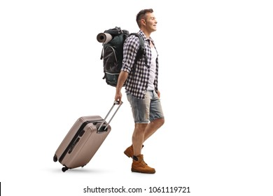 Full length profile shot of a tourist with a backpack and a suitcase walking isolated on white background