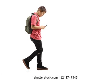 Full length profile shot of a trendy schoolboy walking and looking at a mobile phone isolated on white background