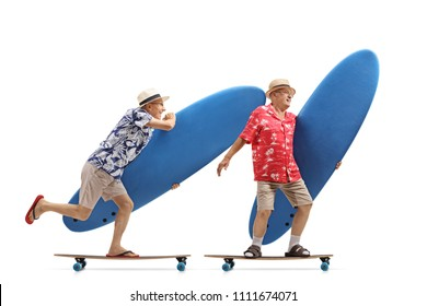 Full length profile shot of two elderly tourists with surfboards riding longboards isolated on white background