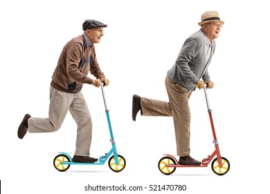 Full length profile shot of two cheerful elderly men riding scooters isolated on white background