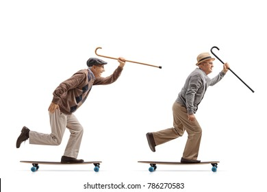 Full length profile shot of two elderly men with canes riding longboards isolated on white background