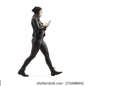 Full length profile shot of a woman in leather clothes wearing a protective medical mask and typing on a mobile phone isolated on white background