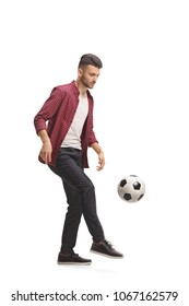 Full length profile shot of a young guy juggling a football isolated on white background