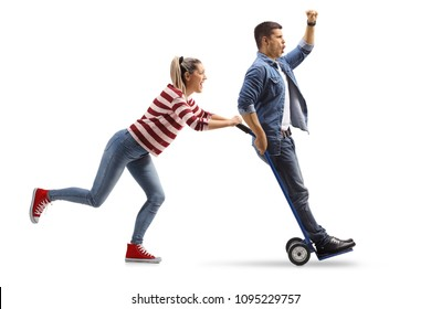 Full length profile shot of a young woman pushing a hand truck with a young man riding on it isolated on white background