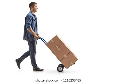 Full length profile shot of a young man pushing a hand truck with boxes isolated on white background