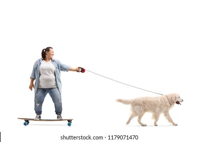 Full length profile shot of a young woman on a longboard walking a dog isolated on white background