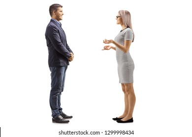 Full length profile shot of a young man and woman standing and having a conversation isolated on white background