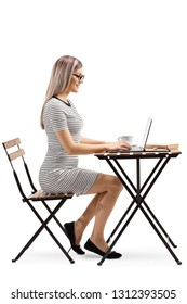 Full length profile shot of a young woman sitting at a table with coffee and working on a laptop isolated on white background