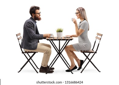 Full length profile shot of a young man and woman drinking coffee at a table isolated on white background