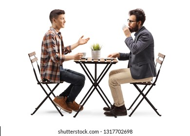 Full length profile shot of a young guy in a cafe talking to a bearded man drinking coffee isolated on white background