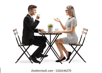 Full length profile shot of a young man in a suit drinking cofee and sitting at a table with a young woman isolated on white background
