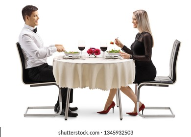 Full length profile shot of a young man and woman eating salad at a table isolated on white background