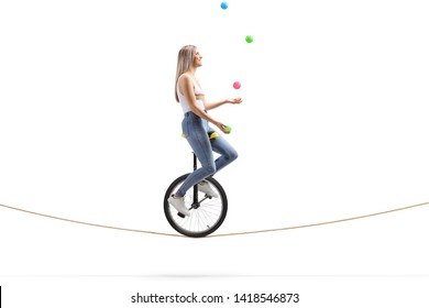 Full length profile shot of a young woman riding a unicycle on a rope and juggling with balls isolated on white background