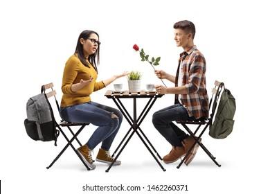 Full length profile shot of a young man giving a present to a happy young woman at a restaurant isolated on white background