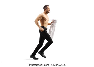Full length profile shot of a young handsome man running shirtless and holding a shirt in his hand isolated on white background